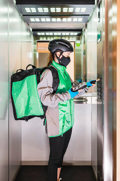 Delivery woman in mask using elevator
