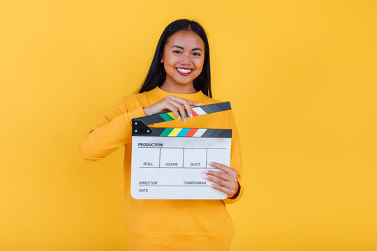 Smiling Asian woman with clapboard in studio