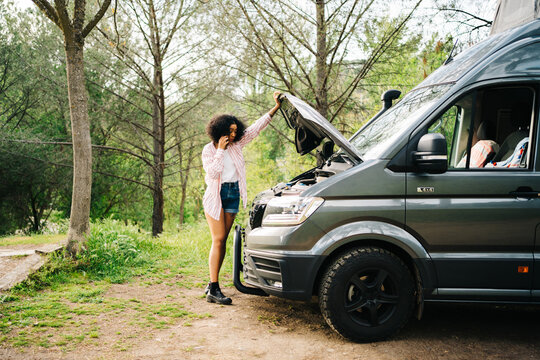 Woman standing near broken car and calling repair service by phone