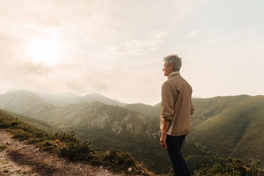Senior woman traveler in mountains at sunrise