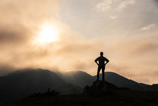 Unrecognizable traveler in mountains at sunrise