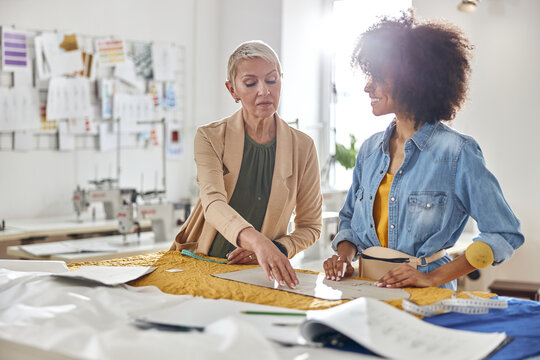Mature lady boss checks sewing patterns made by young African-American seamstress at cutting table