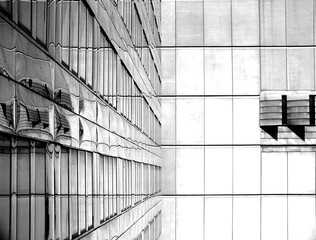 Fototapeta Black and white mirrored shot of a hotel. Shiny metallic tiles can be seen on the left and white and grey tiles in the background obraz