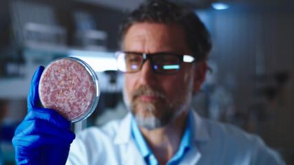 Fototapeta Middle aged man examining Petri dish with lab grown meat obraz