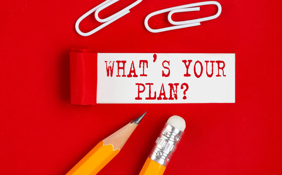 What's Your Plan message written on torn red paper with pencils and clips, business