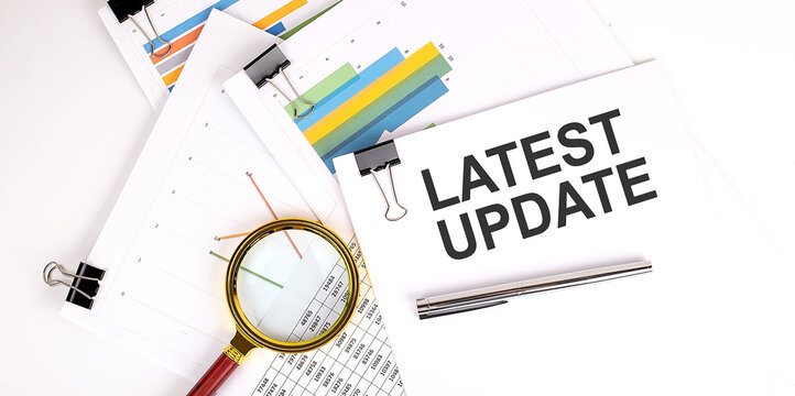 LATEST UPDATE text on white paper on light background with charts paper