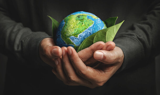 World Earth Day Concept. Green Energy, Renewable and Sustainable Resources. Environmental and Ecology Care. Hand Embracing Green Leaf and Handmade Globe