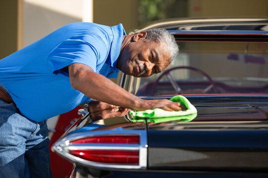 Older man drying off Sport Sedan after detailing