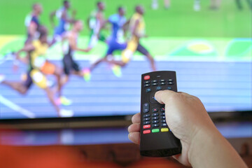 Fototapeta Man watch sports track and field on tv. Close up view on remote control. obraz