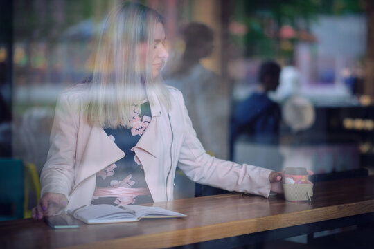 woman in the cafe sits at a table, drinks coffee and looking away. vintage color tone