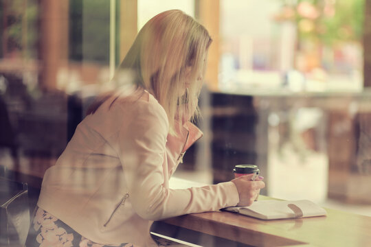 Cafe city lifestyle woman on phone drinking coffee talking on smartphone app sitting indoor in trendy urban cafe. in vintage color tone