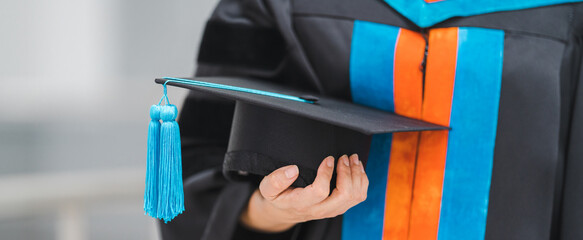 Fototapeta Close-up shot of a university graduate in graduation gown holding a degree certification with mortarboard to shows and celebrates success in the college commencement day. Education stock photo obraz