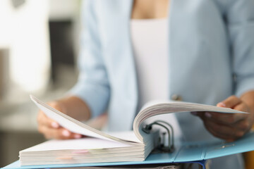 Woman examining information in folder with documents closeup