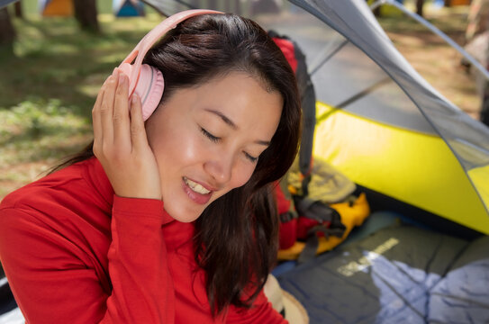 A beautiful woman enjoy listening to music from headphones. She sat in a tent. Backpacking camping In the middle of a beautiful pine forest beside Lake, Pang Oung, Mae Hong Son, Thailand.