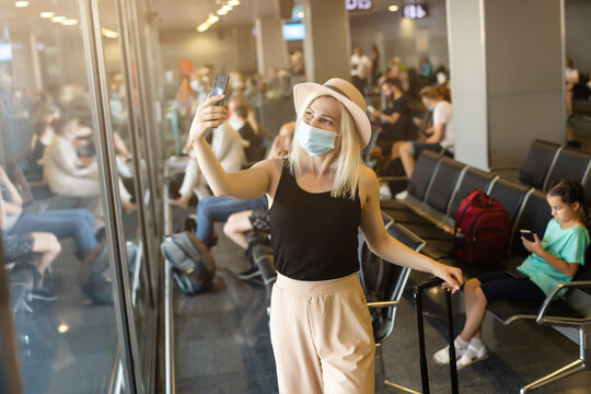 Caucasian traveler girl with medical face mask in airport. Woman wearing a protective mask against coronavirus. Facial hygienic mask for safety outdoor. Environmental awareness or virus spread fear.