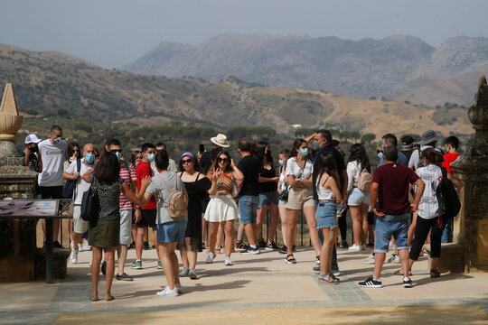 Tourtists look at landscape from a balcony at Alameda del Tajo park, in Ronda