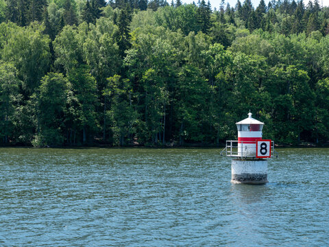 Small lighthouse with background of island covered with trees. Hot summer day.  Shot in Stockholm archipelago, Sweden, Scandinavia.