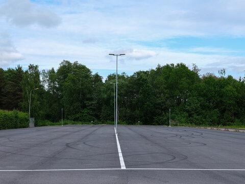Empty car park with skid marks. Woodland background.