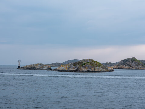 Sea, cliffs and lighthouse on Sweden west coast. Desolate seascape with granite rocks.