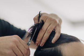 Haircut at a men's barbershop.Haircut with scissors