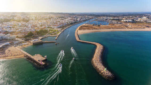 Aerial view from the sky of the Portuguese coastline of the Algarve zone of Lagos city. Boats and ships are moving in the direction of the port.