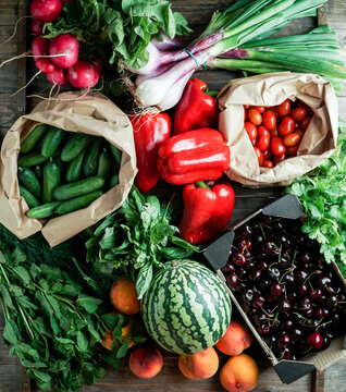 fresh and ripe fruits and vegetables in eco paper packing, cherry, pepper, watermelon,  cerry tomatoes, herbs