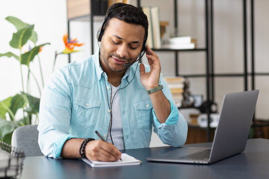 Distance work concept. Young indian man support worker or freelancer uses laptop and headset to communicate with the client, makes notes in a notebook, online learning