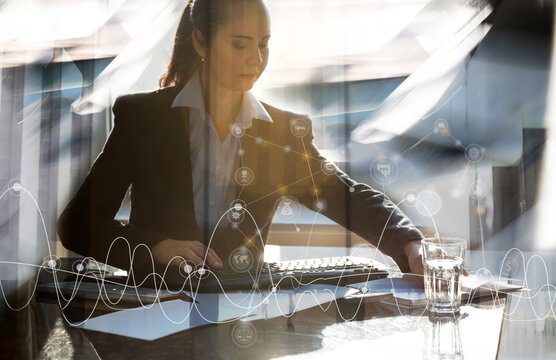 Attractive business woman working by her desk in office against sun light. Business concept