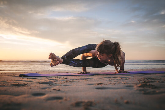 Woman doing Ashtavakrasana yoga at beach