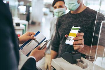 Fototapeta Traveler using vaccine passport for checking in at airport obraz