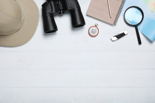 Flat lay composition with different safari accessories on white wooden background, space for text