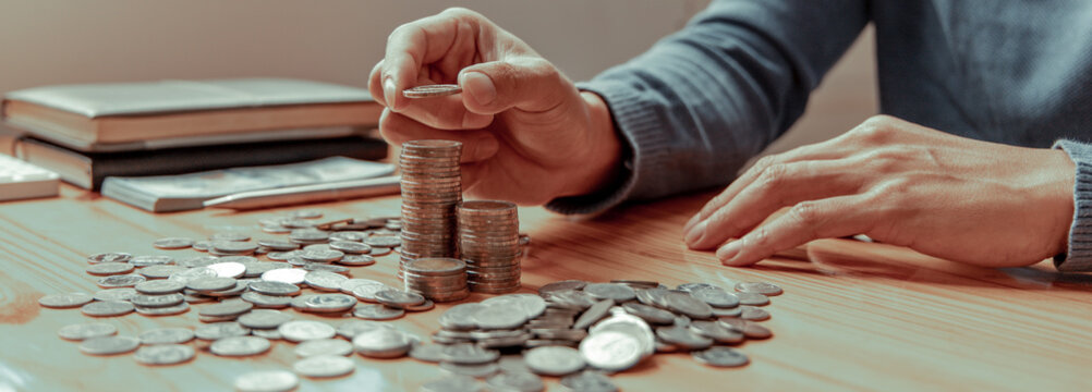 Young man puts the coins on the money bar or on the pile of money to keep for future use, Money management for use when needed, Saving money for future growth and knowing how to manage money.