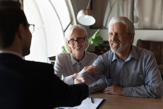 Happy grateful elderly couple of clients thanking real estate agent, lawyer, broker for help with house buying or selling, medical treatment contract, insurance agreement signing, giving handshake