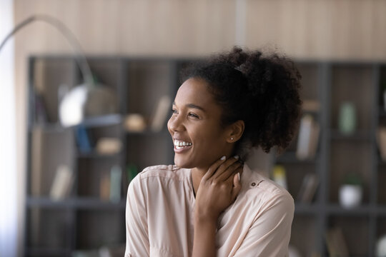 Head shot excited happy dreamy African American woman looking to aside, visualizing good future, overjoyed attractive young female dreaming about new opportunities, having fun, laughing at joke