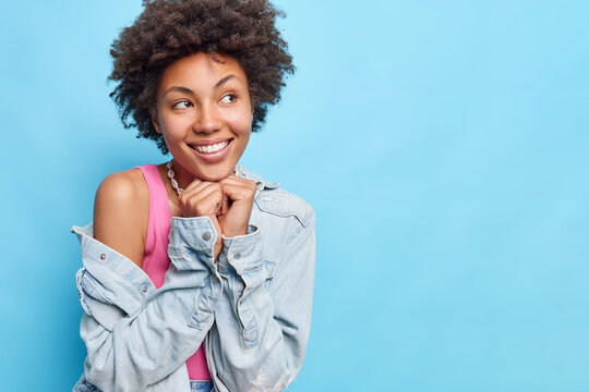 Happy dreamy ethnic lady imagines what she would get for her birthday present, gets interested and anxious, wears pink top and jeans jacket, raises her eyebrow. Isolated over blue background.
