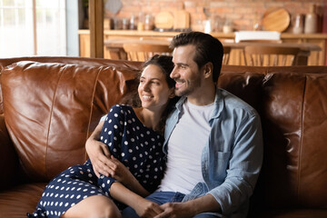 Happy young family couple relaxing on leather couch at home or in stylish hotel apartment. Dating man and woman in love hugging on sofa, talking and smiling, looking away, thinking over good future