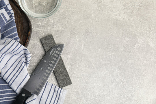 Sharpening stone, knife and water on grey table, flat lay. Space for text