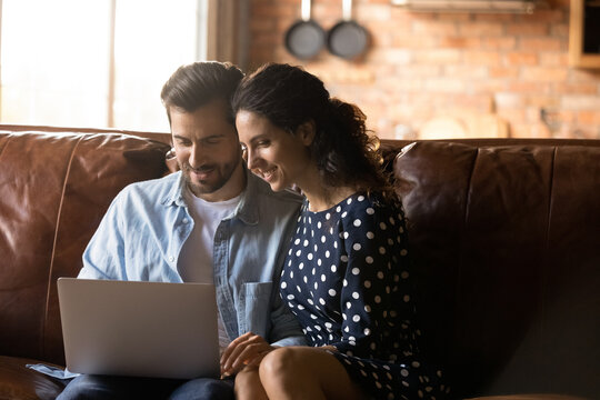 Happy couple sitting on couch at home together, using banking app on laptop, paying insurance, taxes, mortgage bills, planning family budget, making video call, shopping online, browsing internet
