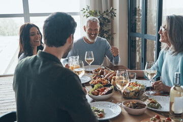 Fototapeta Smiling multi-generation family communicating and enjoying meal while having dinner together obraz