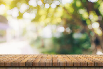 Empty wood table and defocused bokeh and blur background of garden trees with sunlight. product...