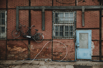 blue door in red brick wall of half-timbered building with tandem bicycle hanging on the wall in docks of Gdansk