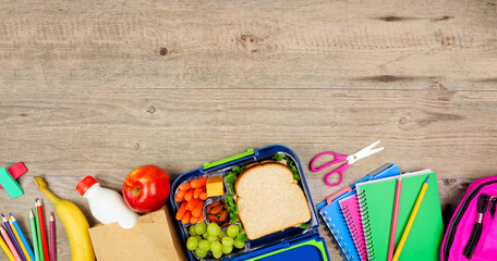 Fototapeta Healthy school lunch and school supplies. Top view bottom border on a wood background. obraz