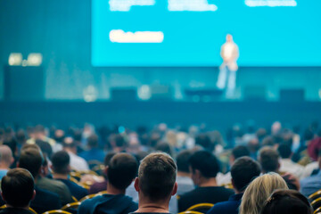 Unrecognizable people listening to speaker during business conference
