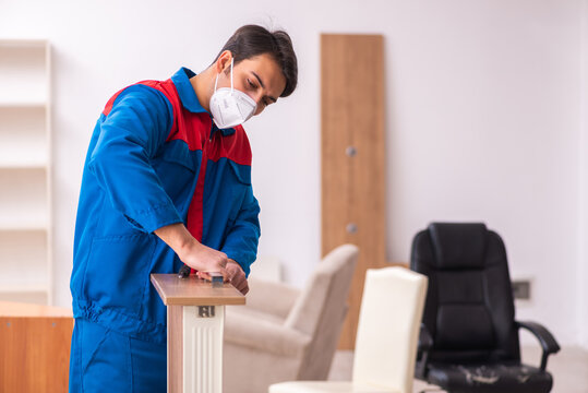 Young male carpenter working in the office during pandemic