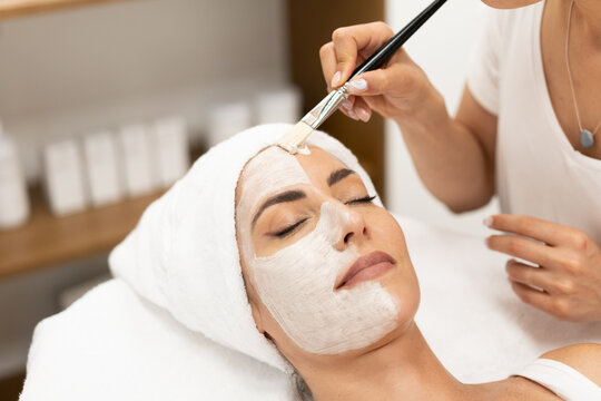 Aesthetics applying a mask to the face of a Middle-aged woman in modern wellness center.