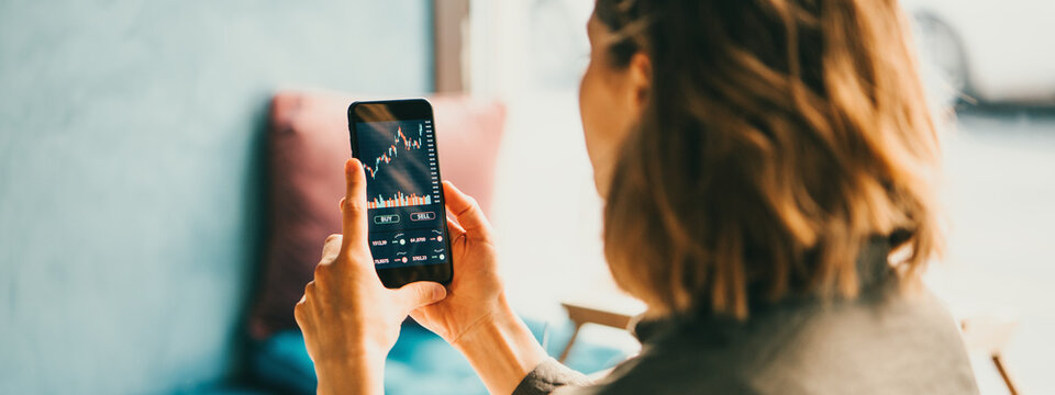 Woman using mobile phone investing application. Stock market investment app in hand. Back view