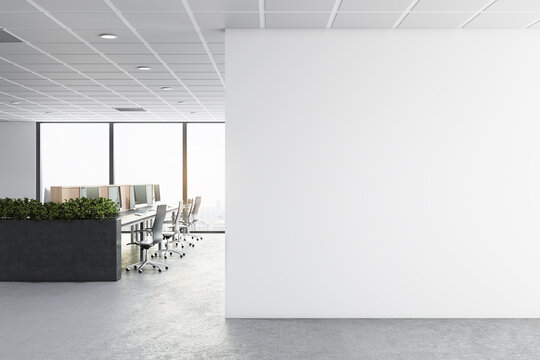 Modern concrete coworking office interior with furniture, window with city view, daylight and empty mockup place on wall. Corporate concept. Mock up, 3D Rendering.