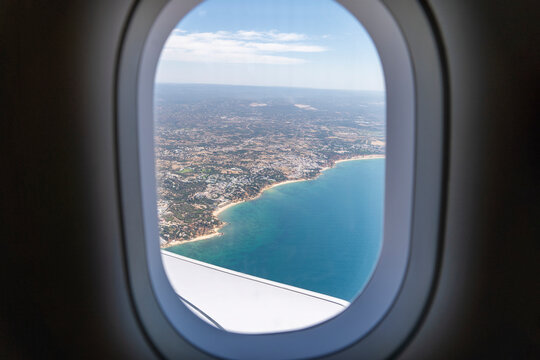 Airplane porthole window with the coast, beach and ocean view from the interior seat. Travel Concept