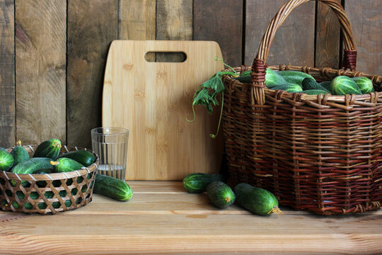 green cucumbers and a cutting board on a wooden table.
