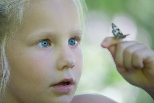 The little girl looks at a butterfly on a hand.